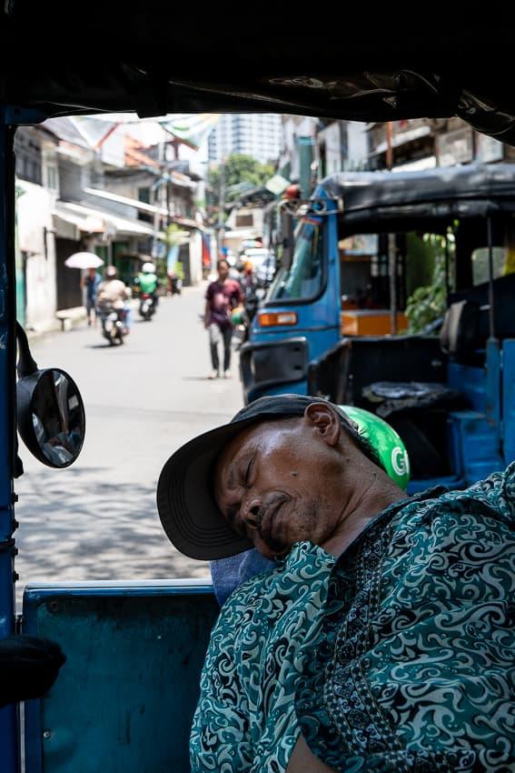 Bajaj driver sleeping on his vehicle