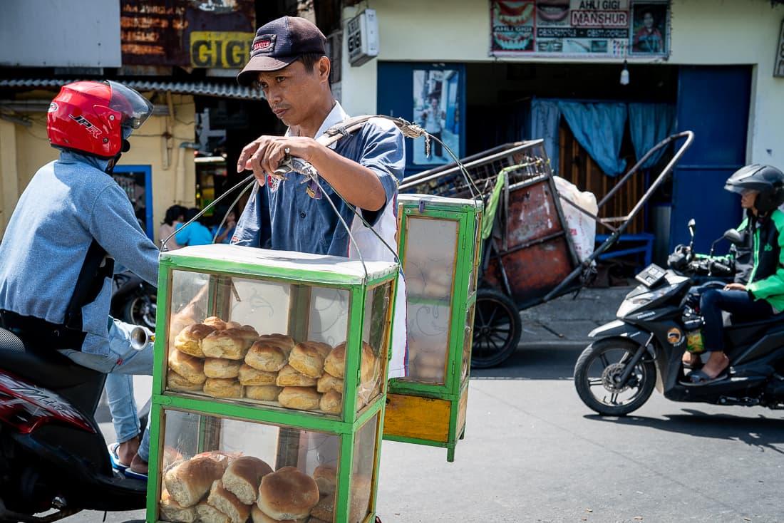 天秤棒でパンを売り歩く若者