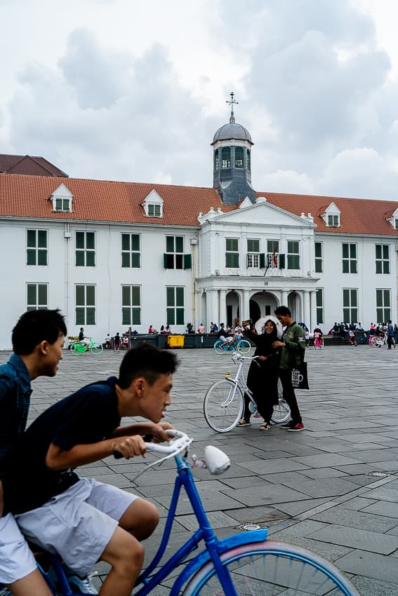 Couple taking a selfie and a bicycle in Fatahillah Square