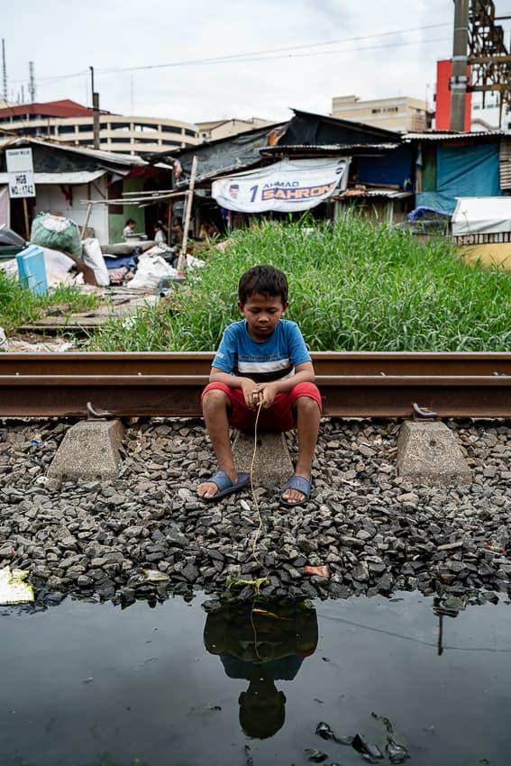 水溜りの横に腰掛けた男の子
