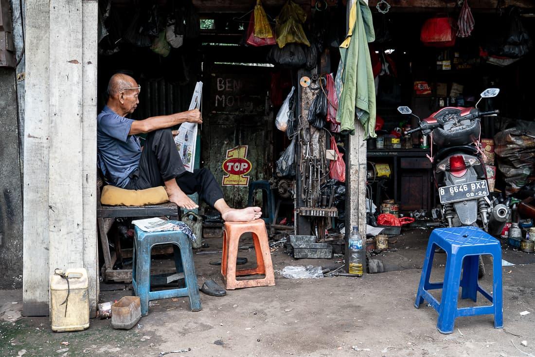 整備工場で新聞を読む男