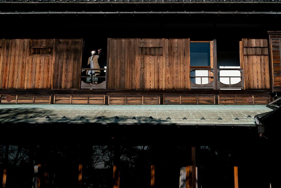 旧朝倉家住宅の2階の窓から指差す女性