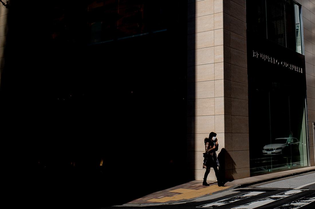 Woman walking in front of a shadowed building