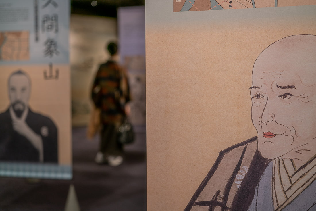 Woman in a kimono seen between the portraits