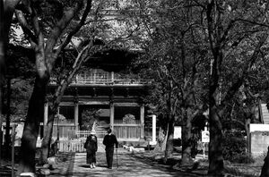 Two figures walking in front of Nio-Mon Gate