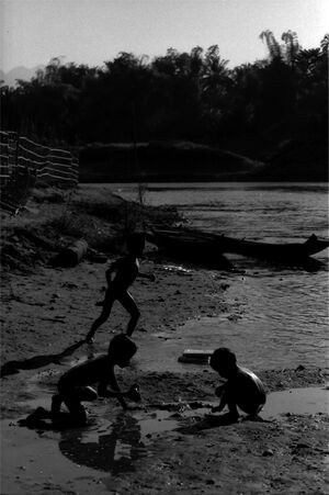 Silhouetted kids playing around on dry riverbed