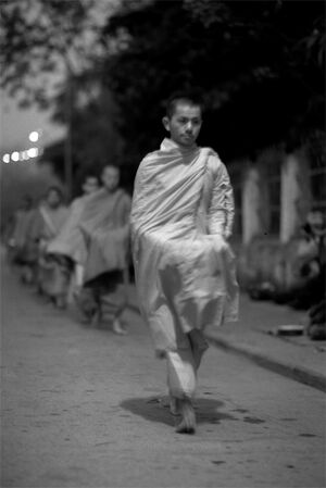 Buddhist monks walking dim street for alms