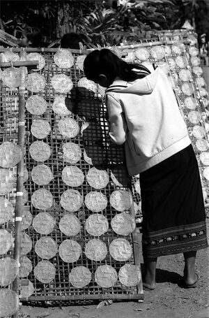 Girl drying rice cakes
