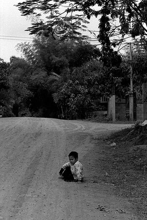 Boy sitting down on the edge of dirt road