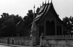 寺院の横を日傘を差して歩く僧侶