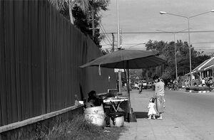 屋台の前に立ち止まるお母さんと赤ん坊