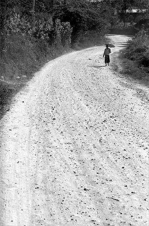 Woman walking dirt road with sunshade