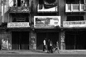古びたビルの前を歩くサリーを着た若い女性