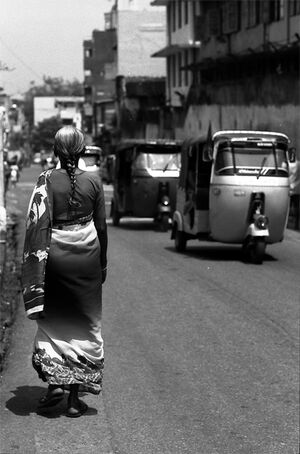 Three wheelers passing by woman with saree