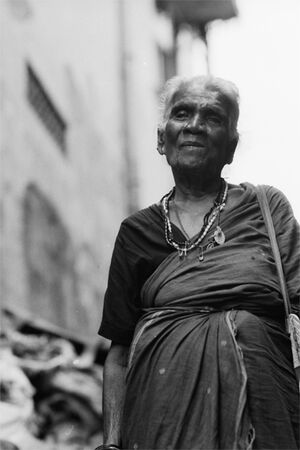 Older woman walking with saree and necklace