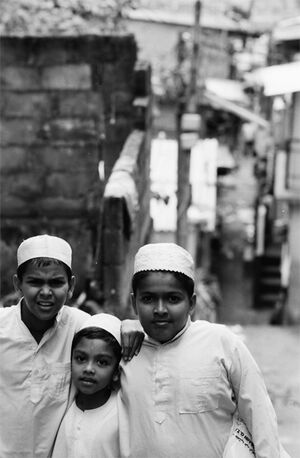 Three boys wearing white Taqiyah