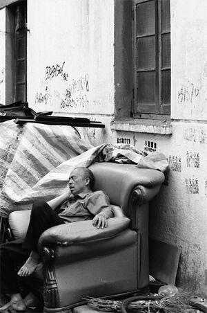 路地に放置されたソファで寝る男