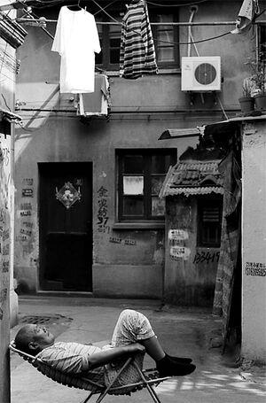 洗濯物の下で昼寝する年配の男