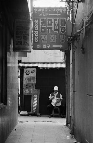 路地裏で新聞を読む男