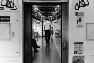 電車の中でうなだれながら歩く男