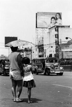 ひとつの日傘に入ったお母さんと娘