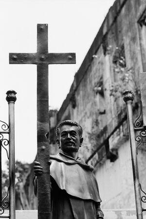 手に大きな十字架を持つ聖職者の像
