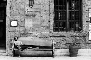 Man taking nap on bench placed in front of souvenir shop
