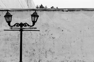 Street lamp standing in front of tall wall