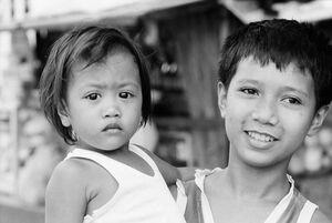 Little girl held by elder boy