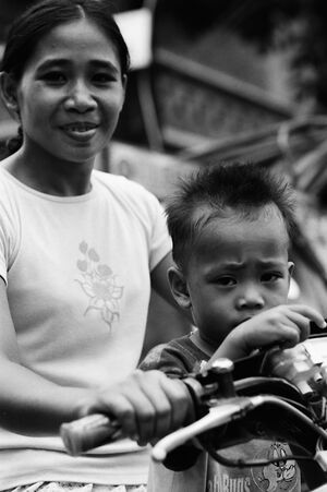 Boy riding motorbike with mother