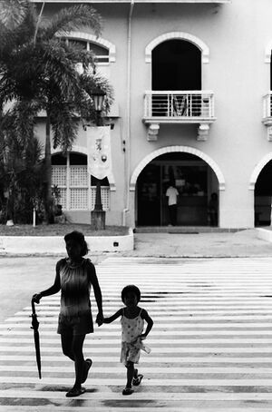 Parent and child crossing street with closed umbrella