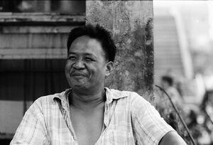 市場の通路脇に腰を下ろして休んでいた男