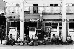 ガソリンスタンdの屋根の下で休息する行商人たち