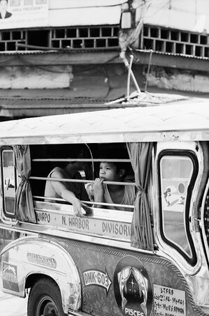Boy looking into distance from jeepney