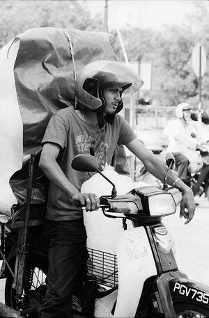 Men carrying big burden with motorbike