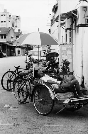 Trishaw driver taking a nap on vehicle