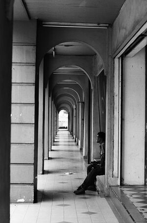 Man sitting alone in deserted passage