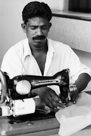 Man working with an old sewing machine