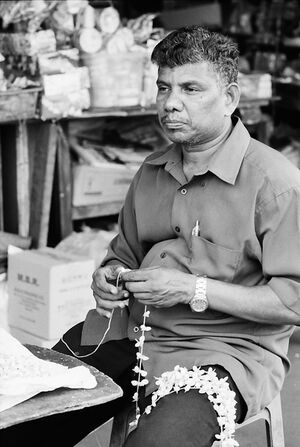 Man weaving garland
