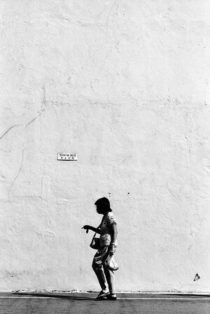 Woman walking in front of tall wall