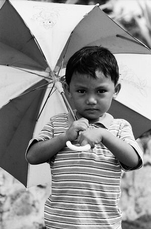 Boy holding striped umbrella