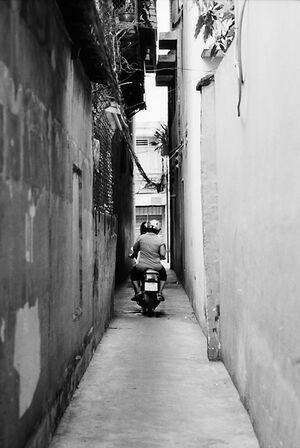 壁に挟まれた路地を走るバイク