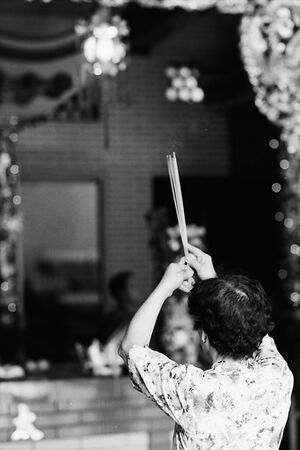 Woman praying with long incense sticks