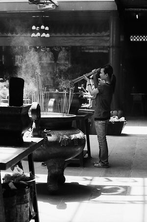 Woman lighting incense sticks on fire