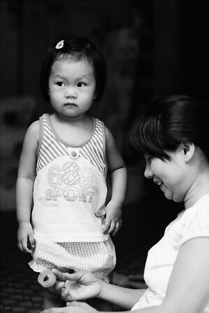 Girl standing beside mother