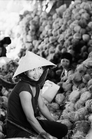 Woman smiling beside coconuts