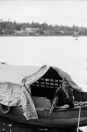 Older woman sitting on moored boat