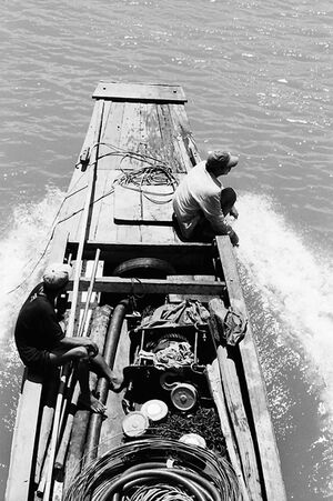 水飛沫を上げるボートの舳先に腰掛けた男