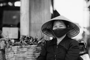 Woman wearing conical hat and black mask