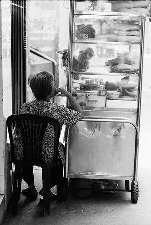 ガラス箱の横に腰掛けた老婆
